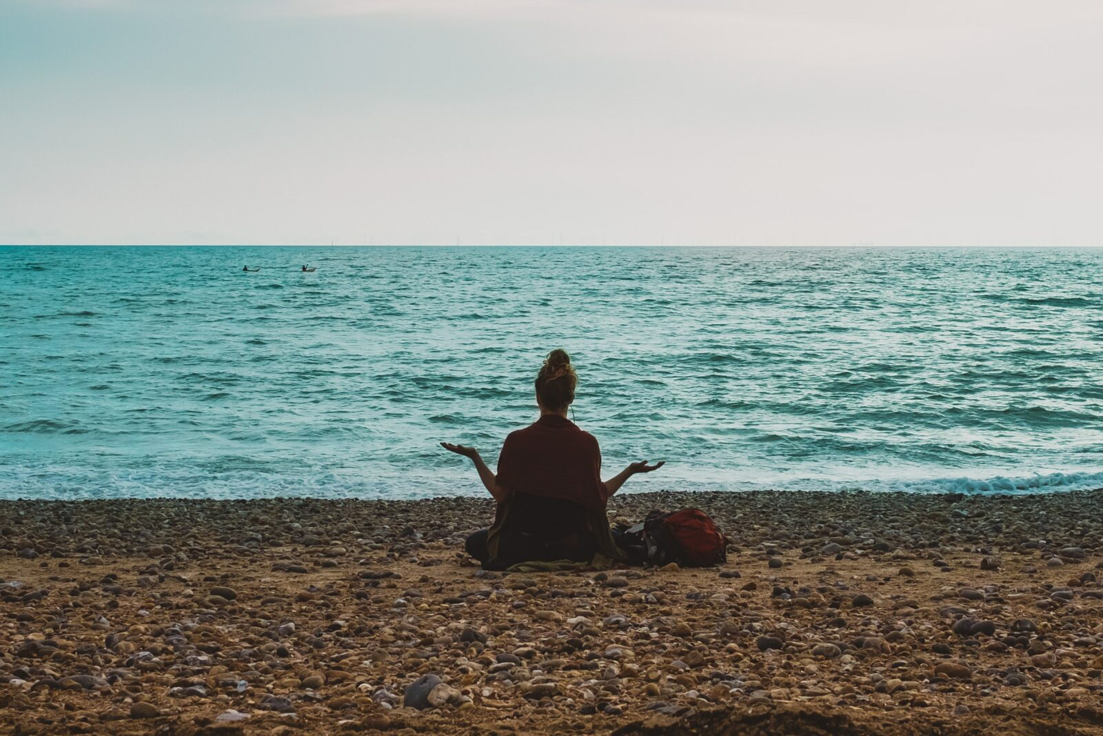 A person sitting on a beach in front of the water meditating. It shows the importance of mastering the art of 'yes and...'