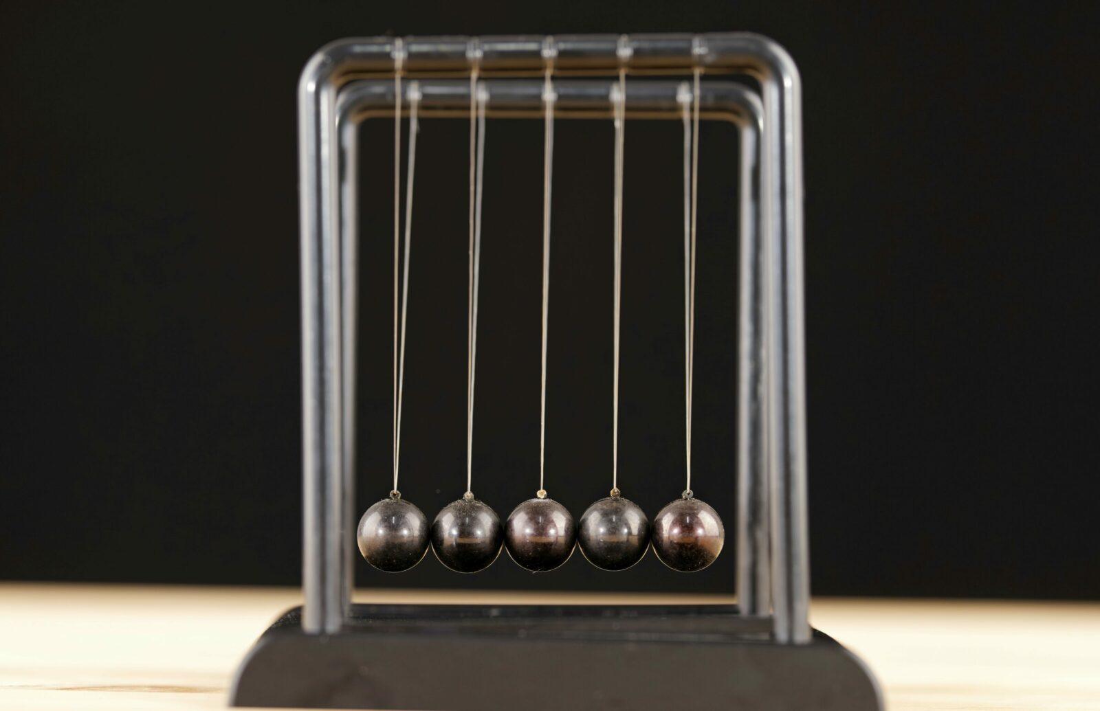 A Newton's cradle sitting on a desk