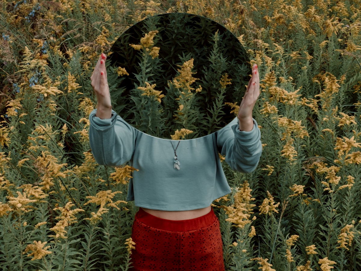 A person standing in a field of flowers with a mirror in front of their face to show the importance of tackling your self-centered tendencies