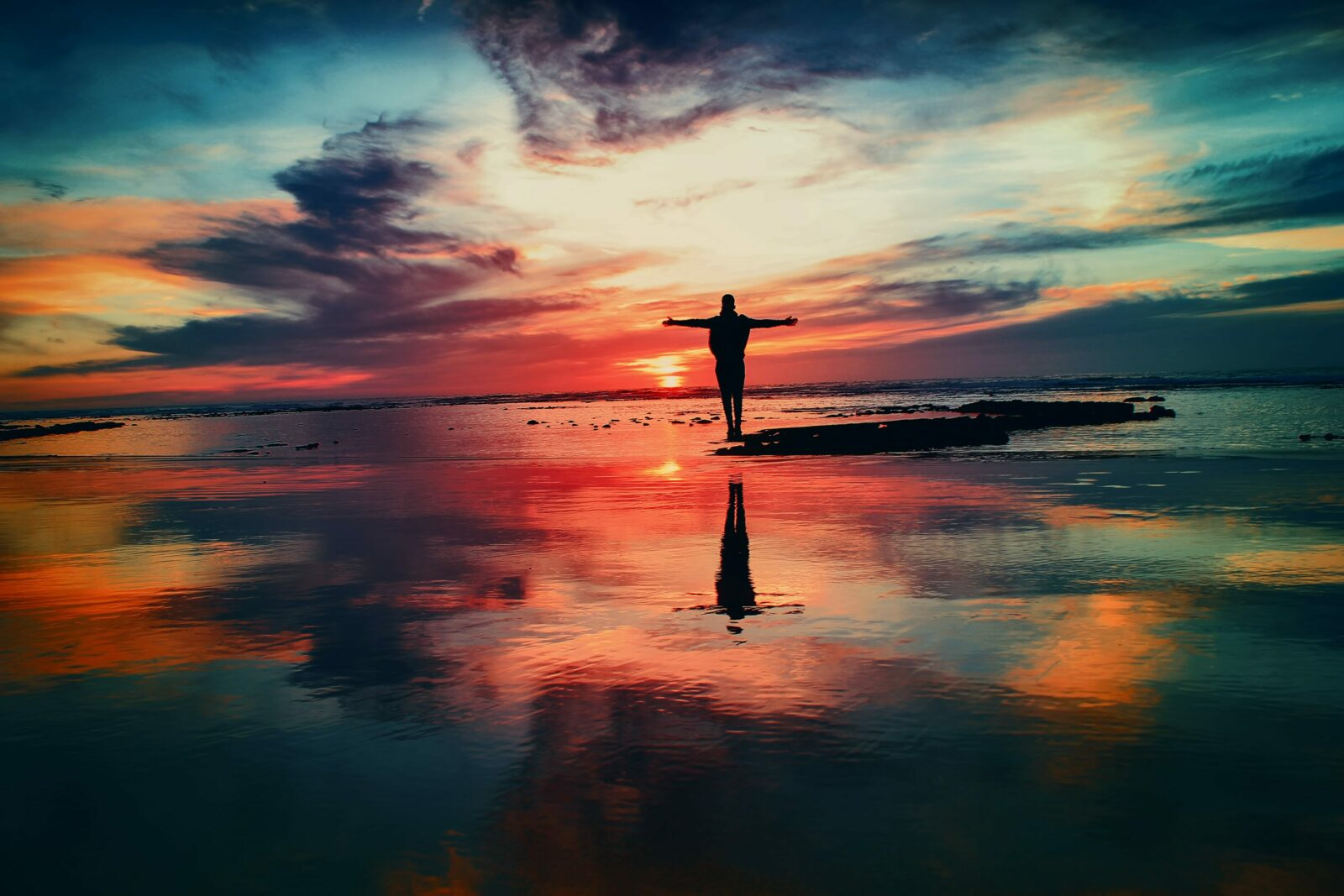 Someone standing on the beach during sunset, demonstrating the value of having a coach