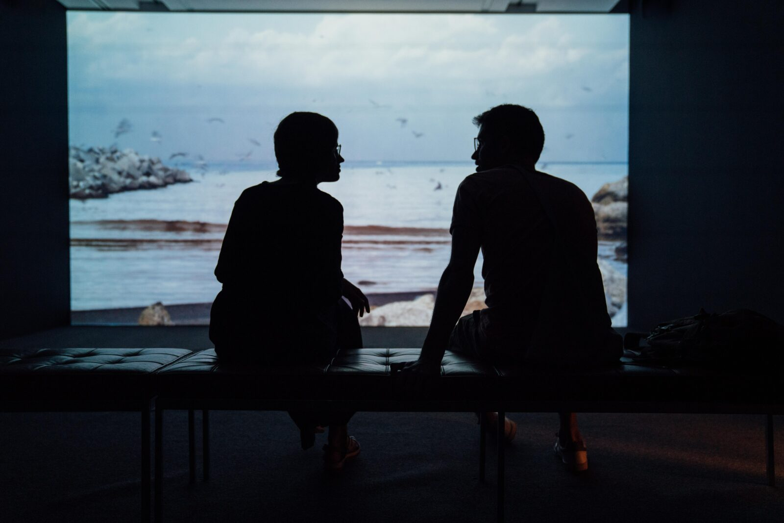 The silhouette of two people sitting and talking together, showing the importance of trying to learn from those around you