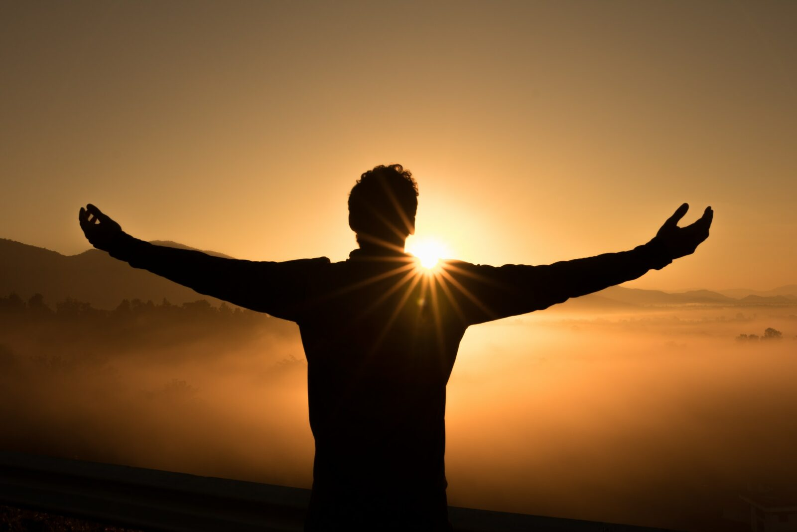 Someone standing in front of a sunrise with their arms outstretched